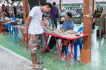 lucky charm: Bangkok, Thailand - April, 09, 2017 : Unidentified man are looking amulets distribution panel in Taling Chan Floating Markett at Bangkok, Thailand.