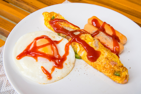 Omelet, grilled sausages, tomato on a white plate Stock Photo