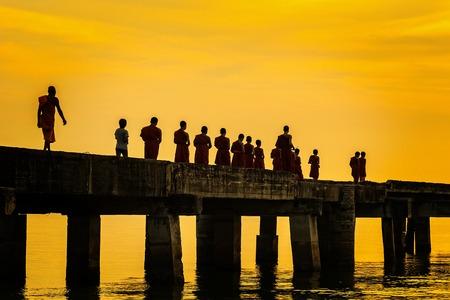 Chon Buri, Pattaya, Thailand - April, 29, 2017 : Buddhist monks are walking on a bridge in the evening sunset.Bridge of Temple Djittabhawan at Pattaya, Thailand.Long bridge extends into the sea. Editorial