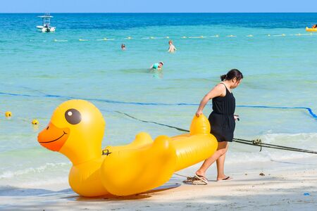 Rayong, Thailand - April, 28, 2017 : Unidentified name Female tourists are dragging Yellow Duck swim tube on the beach on the beach at the Koh Samet island, Rayong, Thailand Editorial
