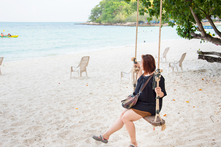 Rayong, Thailand - April, 29, 2017 : Beautiful woman sitting on a swing on the beach at the Koh Samet, Rayong, Thailand