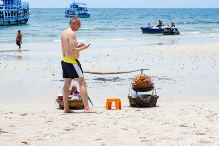 Rayong, Thailand - April, 29, 2017 : Unidentified name Foreign tourists waiting for the trader selling Somtum Grilled Chicken, Local Food on the Samet Island Beach, Rayong, Thailand