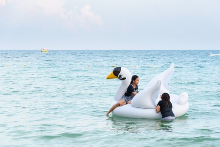 Rayong, Thailand - April, 28, 2017 : Unidentified name Tourists are playing in the sea with Inflatable whiye swan swim tube at the Koh Samet island, Rayong, Thailand