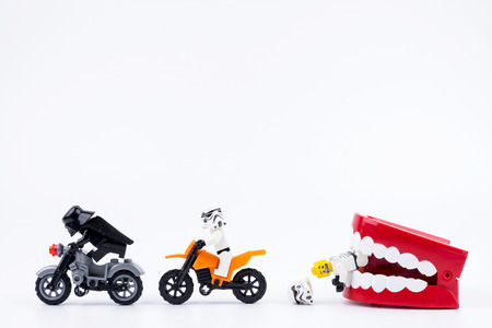 Nonthabure, Thailand - May, 17, 2017 : Lego Darth Vader and Lego stormtrooper riding a motorcycle red plastic chattering teeth being bitten isolated on white background.