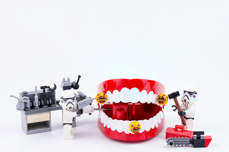 Nonthabure, Thailand - May, 17, 2017 : Lego stormtrooper helping get disinfect of bacteria on red plastic chattering teeth isolated on white background.