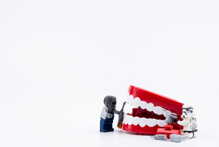 Nonthabure, Thailand - May, 17, 2017 : Lego stormtrooper helping repair the red plastic chattering teeth isolated on white background.