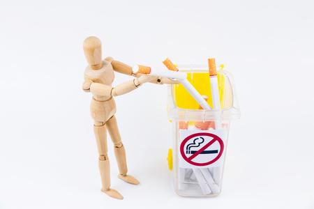 Wooden puppet take the cigarettes to dumps.No Smoking Day background.Anti smoking Stock Photo