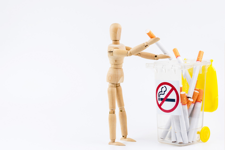 Wooden puppet take the cigarettes to dumps.No Smoking Day background.Anti smoking Stock Photo