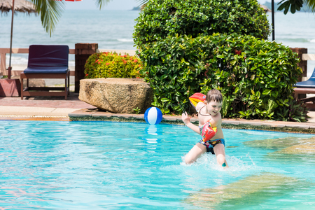 trat: Trat, Thailand - May, 21, 2017 : Unidentified name Boys swimsuit floating and playing with ball in the swimming pool at Klong Prao Resort in Prao Beach Koh Chang island Trat, Thailand.