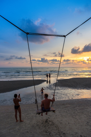 trat: Trat, Thailand - May, 20, 2017 : Unidentified name Father and baby sit on a swing watching the sunset on the beach at Klong Prao Resort in Prao Beach Koh Chang island Trat, Thailand.Concept family