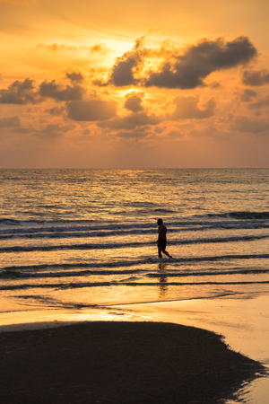 trat: Trat, Thailand - May, 20, 2017 : Unidentified name man walks into the sea at sunset with beautiful clouds on Koh Chang, Thailand