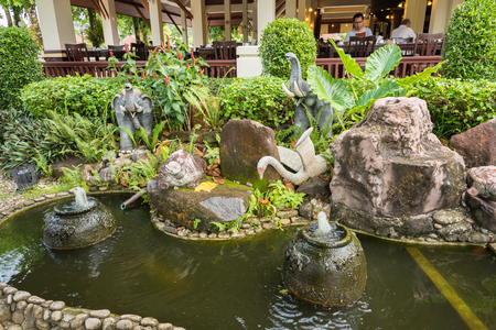 trat: Trat, Thailand - May, 21, 2017 : Animal stone sculptures decorative fish pond in a garden  at Klong Prao Resort in Prao Beach Koh Chang island Trat, Thailand. Editorial