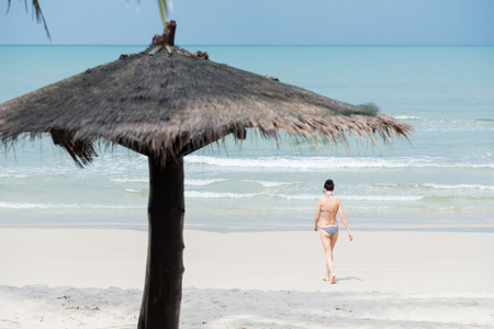 trat: Trat, Thailand - May, 20, 2017 : Unidentified name woman wear a swimsuit bikini walking to the sea at the Prao Beach in Koh Chang island Trat, Thailand.