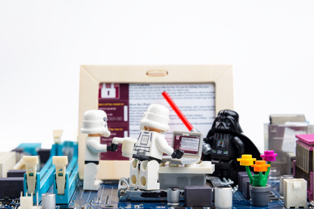 menace: Nonthaburi, Thailand - June, 03, 2017 : Lego star wars stormtrooper learning the system of malware, ransomware WannaCry on a computer motherboard.