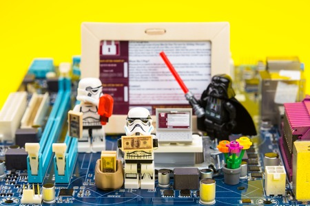 menace: Nonthaburi, Thailand - June, 03, 2017 : Lego star wars stormtrooper Is holding the money fromf malware, ransomware WannaCry on a computer motherboard.