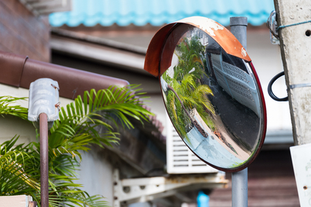 concave: Close up traffic curve mirror at dangerous curve road with street reflection in the mirror at Koh Kret, Nonthaburi, Thailand