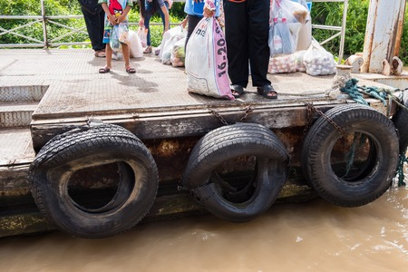 oxidation: Nonthaburi, Thailand - June, 11, 2017 : Old tires used as a bumper for boats or big truck tires used for bump stop in a commercial dock at Koh Kret, Nonthaburi, Thailand