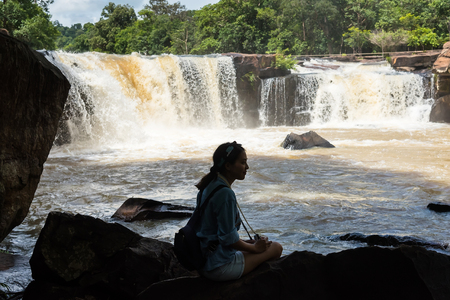 streamlet: Chaiyaphum, Thailand - July, 01, 2017 : Unidentified name tourist woman photographers sit on the rocks at Tat ton Waterfall in early rainy season in Chaiyaphum, Thailand
