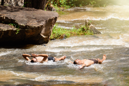 streamlet: Chaiyaphum, Thailand - July, 01, 2017 : Unidentified name tourist man playing water at Tat ton Waterfall in early rainy season in Chaiyaphum, Thailand Editorial