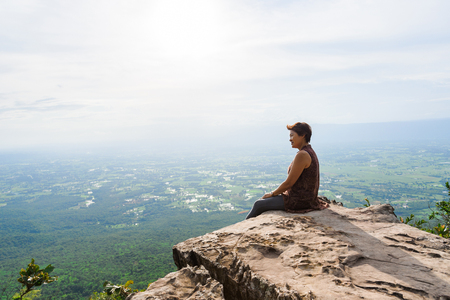 Chaiyaphum, Thailand - July, 01, 2017 : Unidentified name tourist woman sits on a cliff edge on the top of mountain with gorgeous view at Chaiyaphum, Thailand