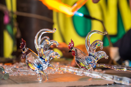 Phetchabun, Thailand - July, 15, 2017 : Chickens glass animal with a flaming blowtorch on new glass art piece at Khao Kho Phetchabun Thailand.