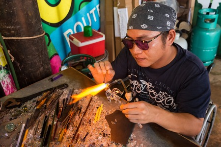 Phetchabun, Thailand - July, 15, 2017 : Handicrafts man making a glass animal with a flaming blowtorch on new glass art piece at Khao Kho Phetchabun Thailand.