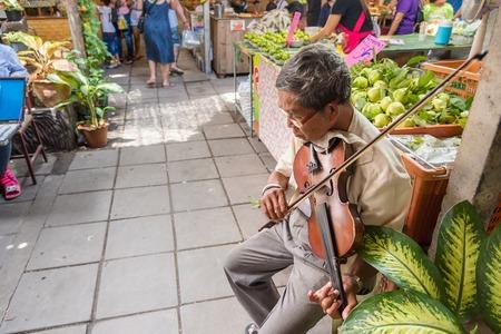 Bangkok, Thailand - July, 30, 2017 : Unidentified name Old man asian musician violinist playing violin in at Khlong Lat Mayom Floating Market Bangkok, Thailand. Editorial