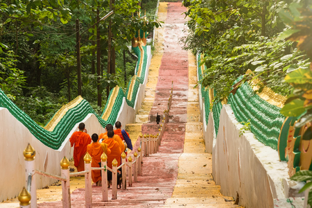 Nan, Thailand - September, 23, 2017 : Unidentified name buddhist monk was walking alms giving ceremony in the morning.Walking down the stairs of Wat Phra That Khao Noi in Nan Province, Thailand