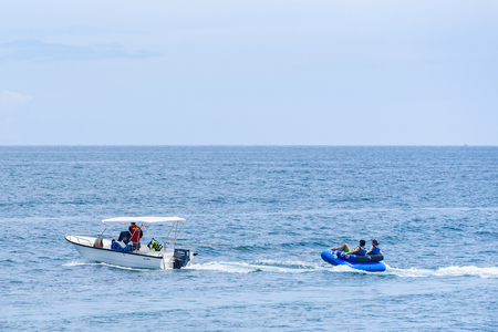 Rayong, Thailand - October, 07, 2017 : Unidentified name the boat driver towing tourist couple on rubber raft player following him in the sea at the Koh Samet island, Rayong, Thailand Editorial