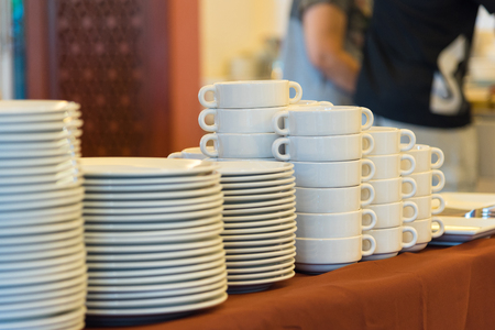 Plates and bowls, white ceramic on a brown tablecloth