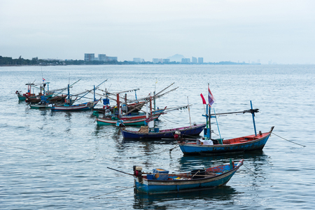 Fishing boats floating in the sea over cloudy sky at Prachuap Khiri Khan, Thailand