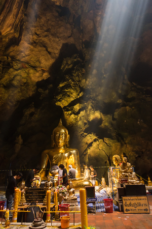 Phetchaburi, Thailand - October, 14, 2017 : Unidentified name Workers are repairing the Golden Buddha with the new gold leaf in Khao Luang Cave at Phetchaburi, Thailand.