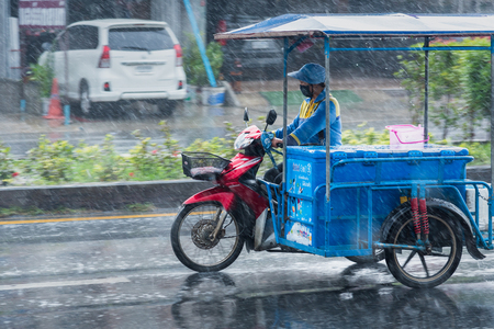 Nonthaburi, Thailand - November, 16, 2017 : Motion Blurred panning photo of Unidentified name people riding tricycle in the rain on road at Nonthaburi, Thailand.