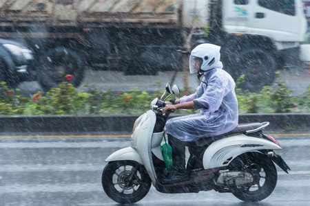 Nonthaburi, Thailand - November, 16, 2017 : Motion Blurred panning photo of Unidentified name people riding motorcycle in the rain on road at Nonthaburi, Thailand.