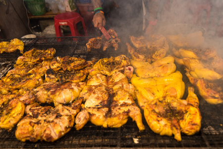 Samut Prakan, Thailand - November, 18, 2017 : Grilled chicken BBQ grilled on burning charcoal on display street food shop in festival night time at Samut Prakan, Thailand.