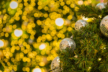 Many mirror balls decorate on green leaves tree and lighting system in a department store in greeting season such as Christmas and New Year festival.Bokeh light backgrounds in Christmas