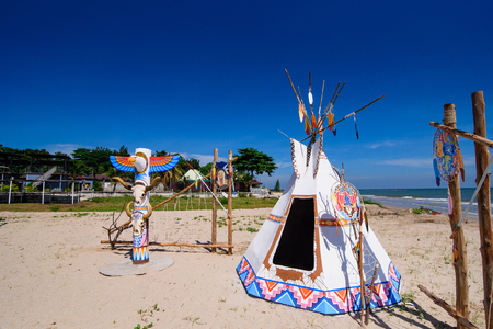 Native american indian tepee and totem pole on the beach blue sky day.Thailand Stock Photo