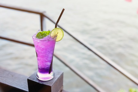 Butterfly pea iced soft drinks with lemon slice and peppermint on top and on the wooden balcony at the riverside restaurant.Thailand
