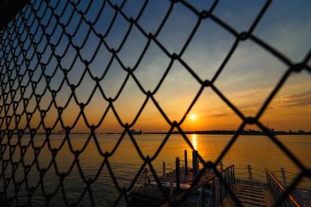 Sunset view through metal net at Chao Phraya River at Samut Prakan, Thailand