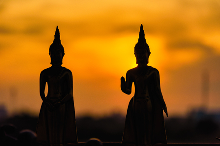 Silhouette buddha statues on blurred sunset background.Thailand Stock Photo