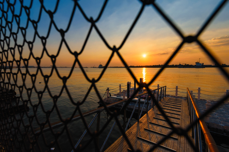 Sunset view through metal net at Chao Phraya River at Samut Prakan, Thailand