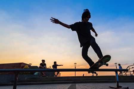 Samut Prakan, Thailand - December, 24, 2017 : Unidentified name man playing skateboard in park by the dam sunset time at Samut Prakan, Thailand.
