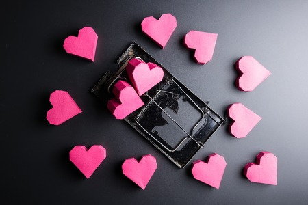 Mousetrap use box red heart shape as bait on black background with copy space.Valentines Day, Day of love