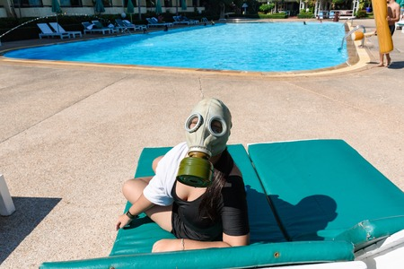 Prachuab Khirikhan, Thailand - December, 24, 2017 : Unidentified name Young women in black swimsuit wearing a gas mask besides a swimming pool in Beach Garden Resort at Cha Am beach of Thailand.