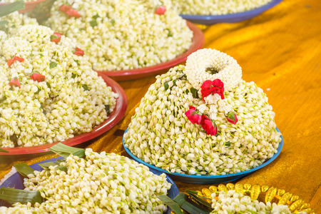 A lot of jasmin garland on a tray consecrated Buddha inside the temple.Thailand Stock Photo