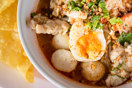 Asian noodle soup with roasted pork and fish ball, Thai style spicy noodle soup.Tom-yum soup Stock Photo
