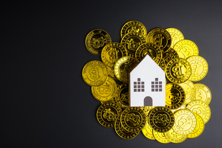 White paper house toy on Cryptocurrency golden bitcoins coin on black background with copy space.Real estate concept, New house concept, Finance loan business concept Stock Photo