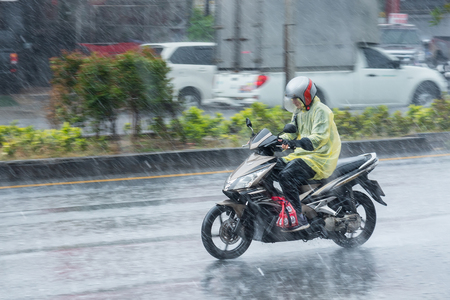 Nonthaburi, Thailand - February, 19, 2018 : Motion Blurred panning photo of Unidentified name people riding motorcycle in the rain on road at Nonthaburi, Thailand. Editorial
