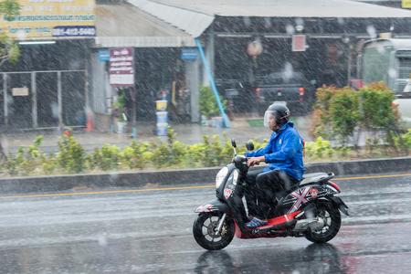 Nonthaburi, Tailandia - 19 de febrero de 2018: Foto de movimiento borrosa panorámica de personas de nombre no identificado montando motocicleta bajo la lluvia en la carretera en Nonthaburi, Tailandia.