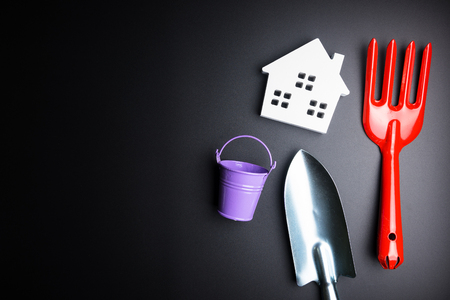 White house toy and gardening tools on black background with copy space.Real estate concept, New house concept, Finance loan business concept, Repair maintenance concept Banque d'images